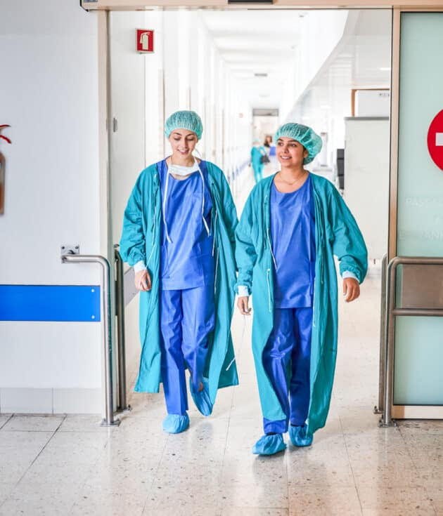 Two students walking out of a hospital wing.