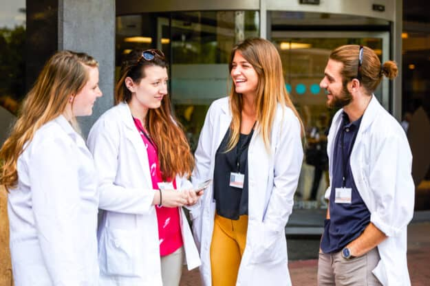 Students chatting outside a hospital.