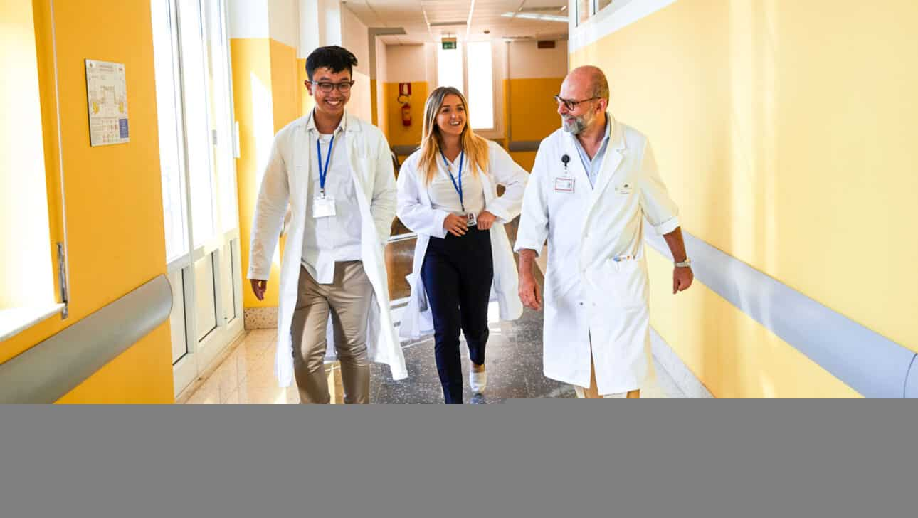 Students walking through the hospital hallway with a doctor.
