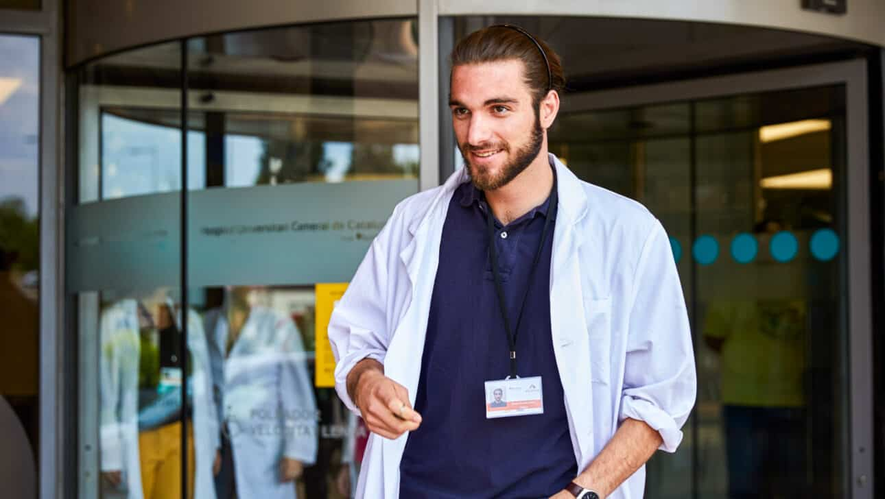 A student standing outside a hospital.