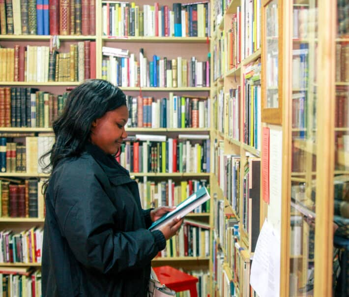 A student examining a book in a library.
