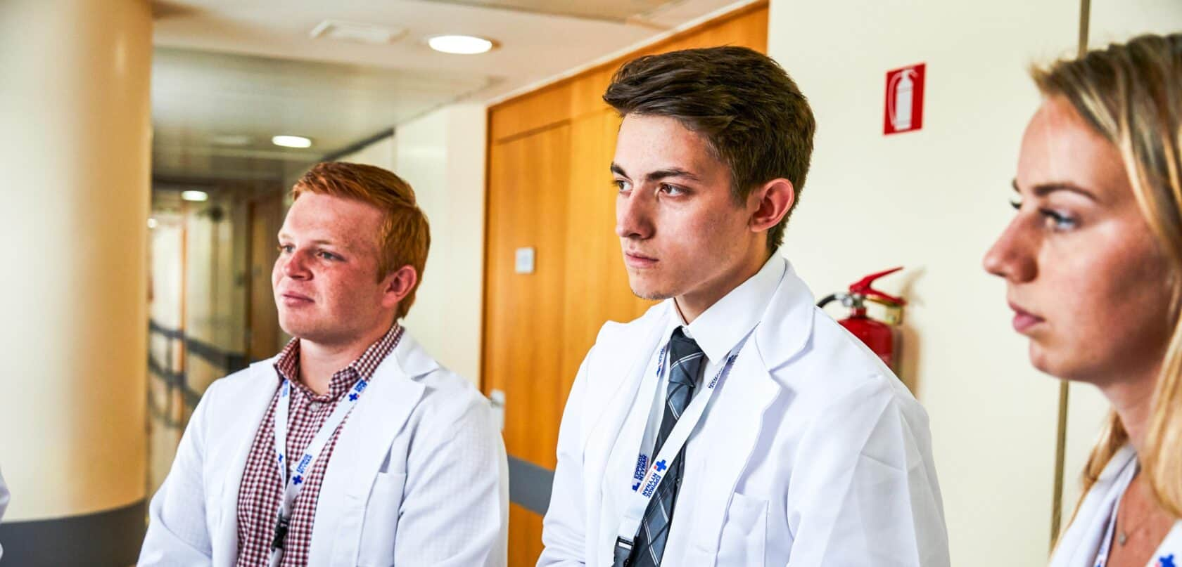 Students listening intently while shadowing in a hospital.