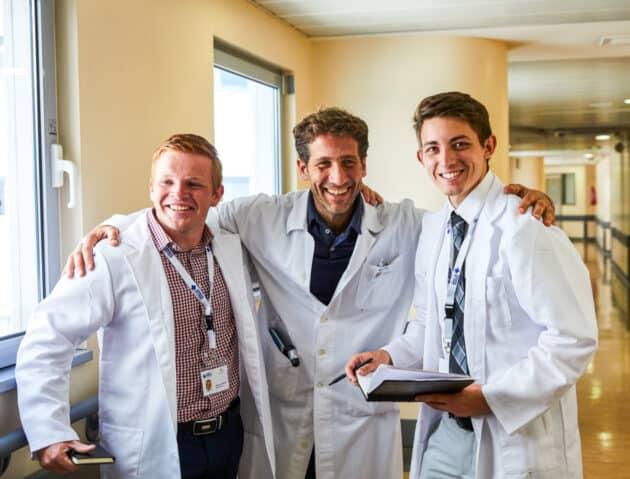 Students smiling with a doctor in the hospital.