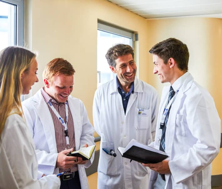 Students speaking to a doctor while shadowing.