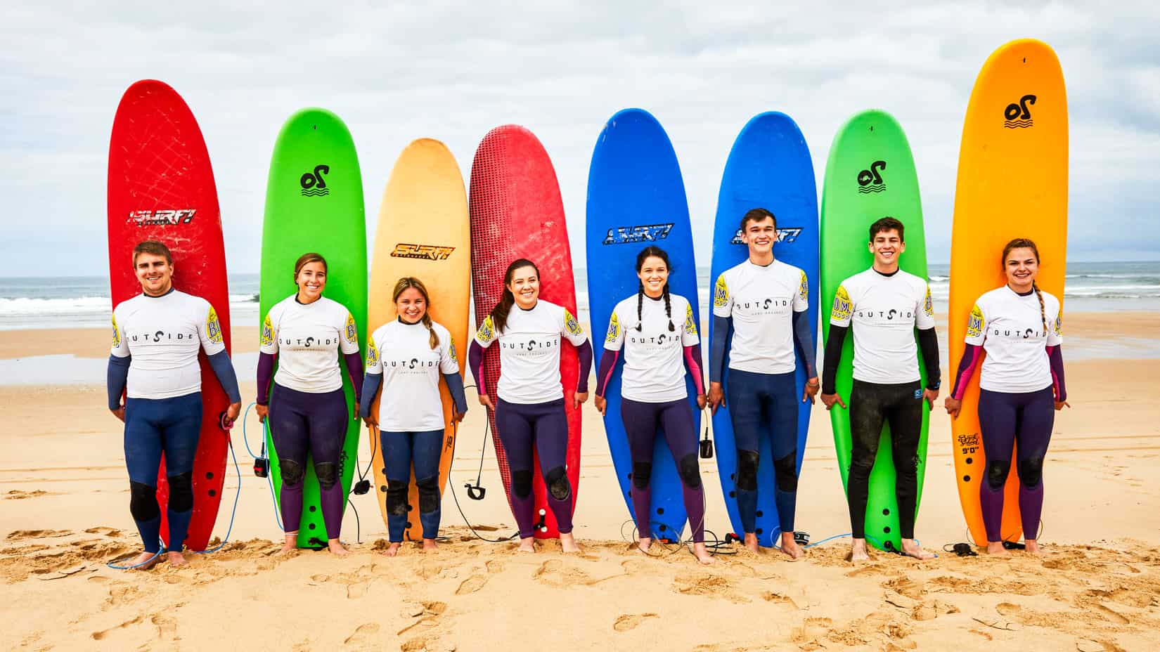 Students lined up with surfboards on the beach. (Lisbon, 2019)