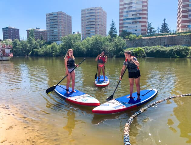 Students paddle boarding on the river beach.