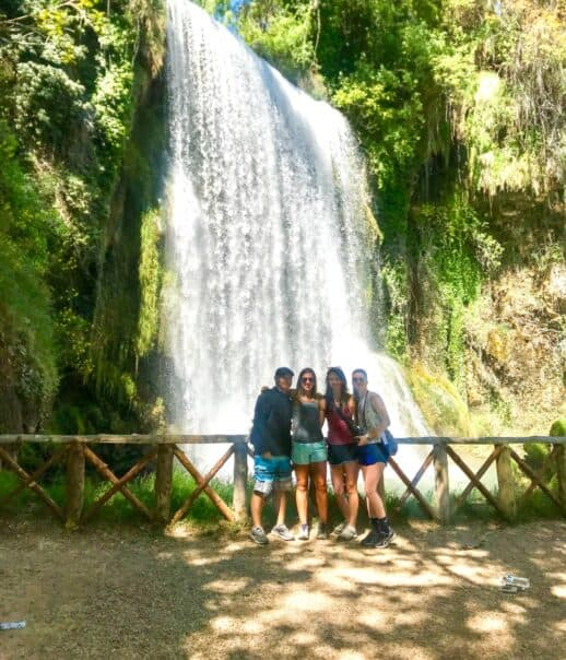 Students standing in front of a waterfall.