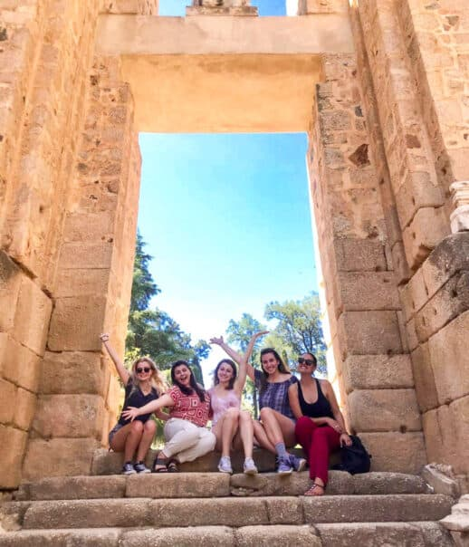 Students sitting in an archway posing for the camera.