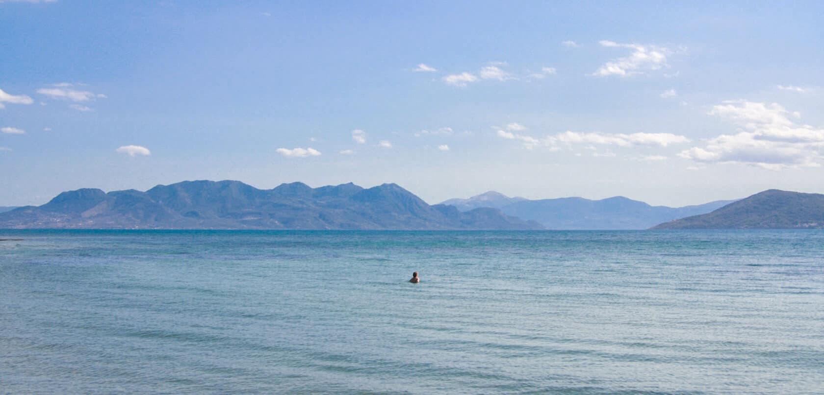 A view of the ocean with mountains in the background.