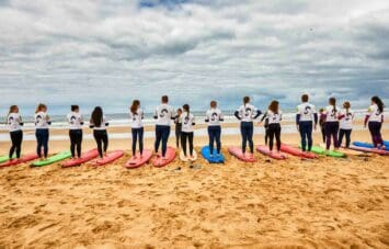 Students standing on surf boards by the ocean.