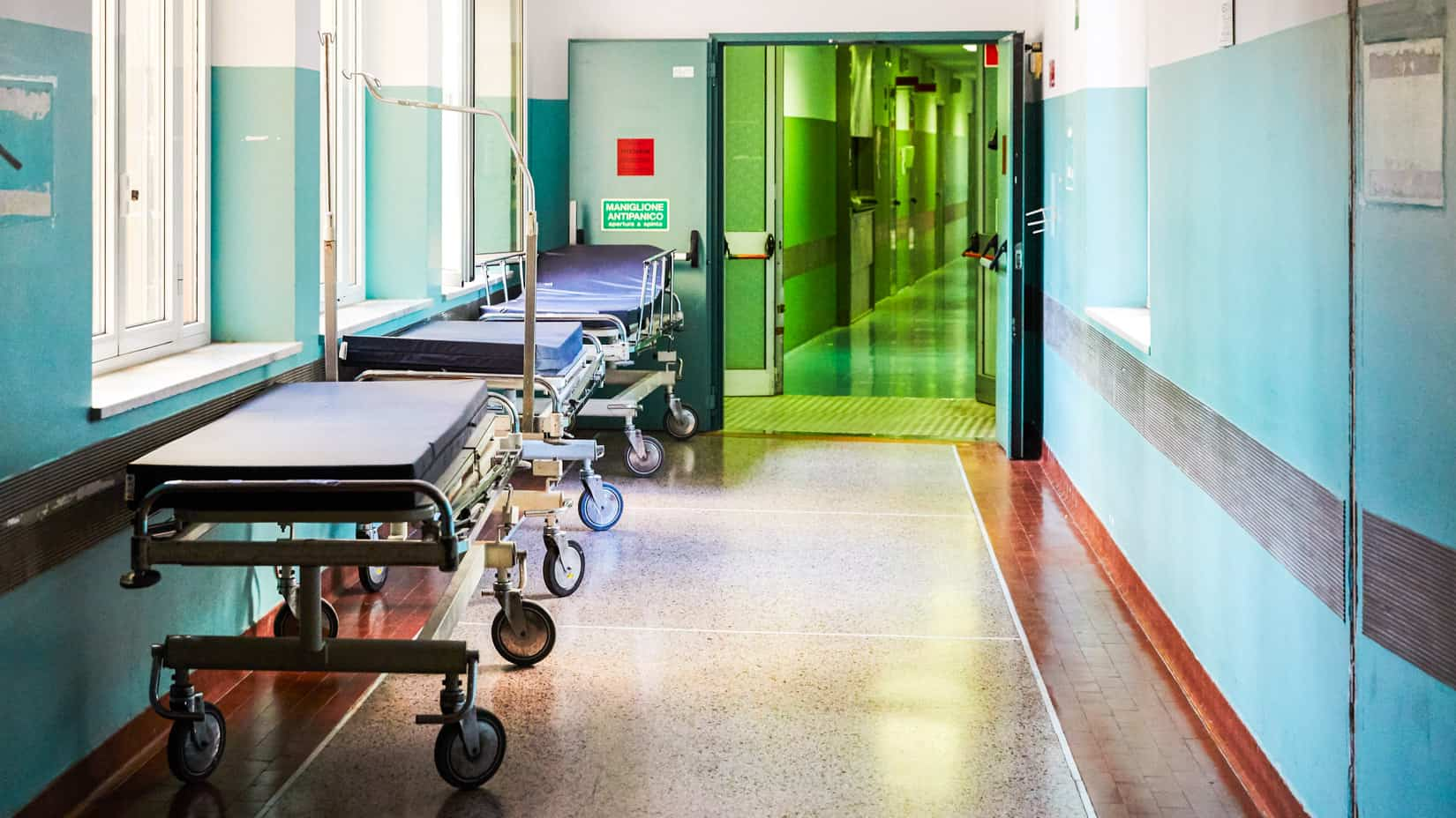 A wing of a hospital with beds.