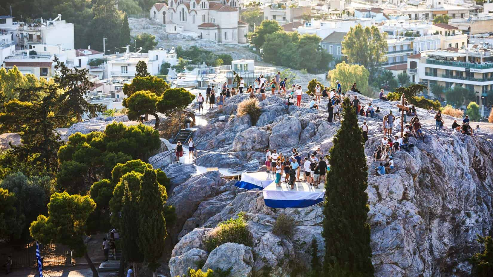 Students on a rock to view the city of Athens from above.