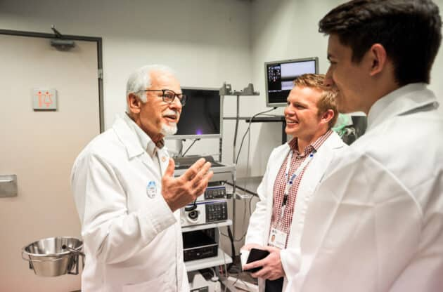 Two students getting the opportunity to speak with a doctor while shadowing.