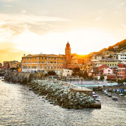 The city of Genoa along the waterfront at sunset.
