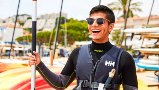 A student smiling and learning how to kayak.